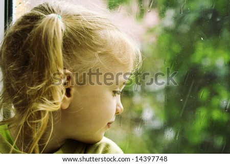 Little girl sitting near the window in the rainy day