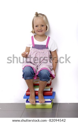 little girl sitting on a stack of books against a wall - stock photo