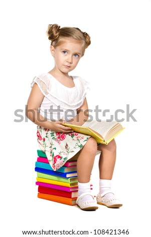 little girl sitting on a stack of books and reading book isolated on white