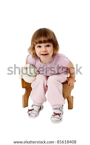 little girl sitting on a wooden stool with a favorite soft toy