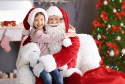 Little girl sitting on authentic Santa Claus' lap indoors