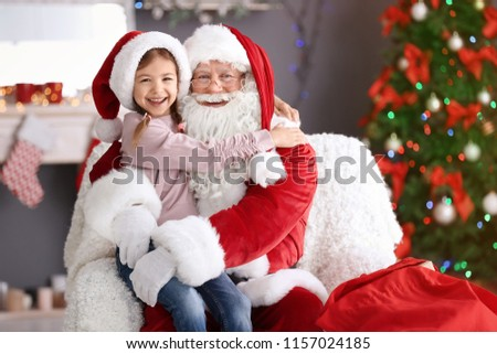 Little girl sitting on authentic Santa Claus' lap indoors #1157024185