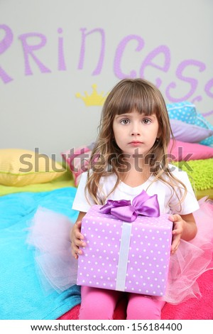 Little girl sitting on bed with gift in room on grey wall background