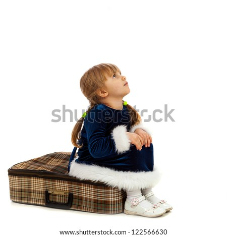 Little girl sitting on big travel suitcase and looking up isolated on white
