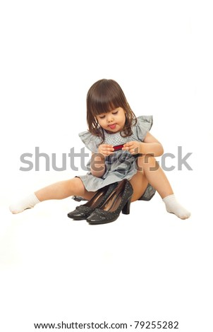 Little girl sitting on floor near big shoes and applying and eating lipstick  isolated on white background