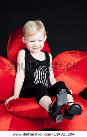 little girl sitting on red armchair