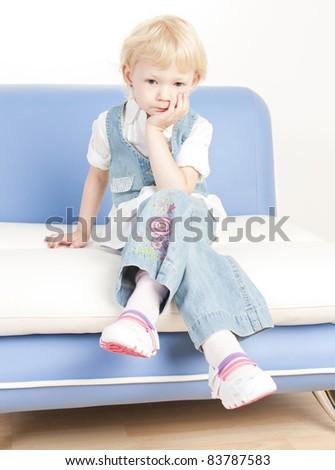 little girl sitting on sofa