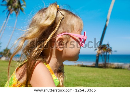 little girl sitting on the beach and watching the sea