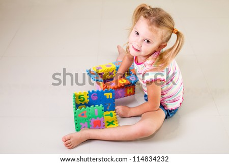 little girl sitting on the floor and building a house out of letters
