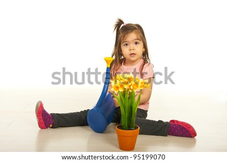 Little girl sitting on the floor and holding watering can isoalted on white background