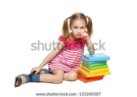 Little girl sitting on the floor leaning on the stack of books, over white background