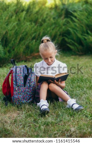 little girl  sitting on the grass and reading book. Pupils of primary school. #1161415546
