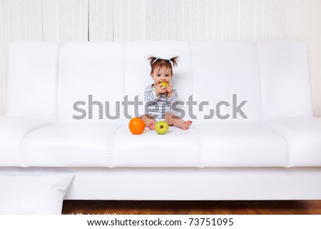 Little girl sitting on the soda with fruit