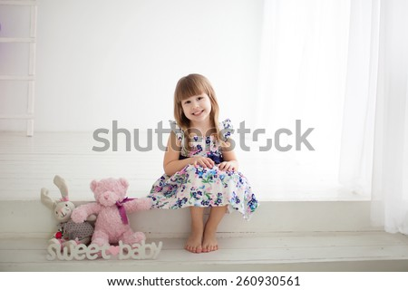 little girl sitting on the steps with toys