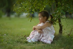 Little girl sitting under a tree on nature
