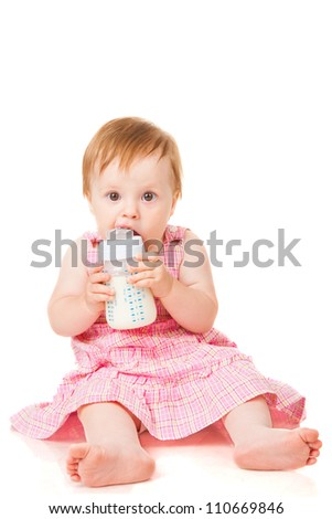 Little girl sitting with a bottle of milk