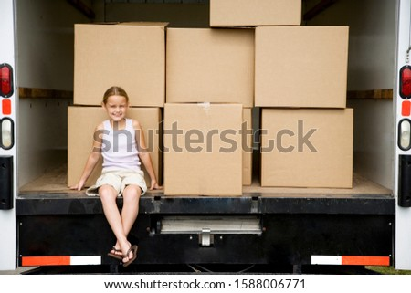 Little girl sitting with packing boxes in the removal van, moving home