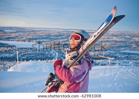Little girl-skier on the hill watching the sunrise at a ski resort in Finland