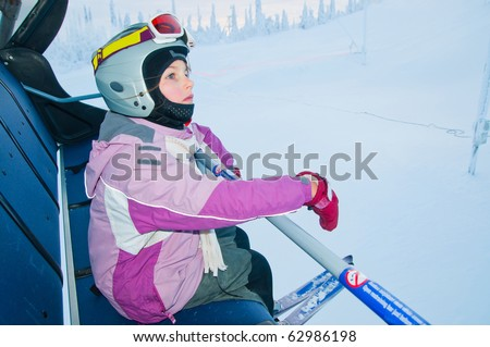 Little girl-skier on the ski lift watching the sunrise at a ski resort in Finland