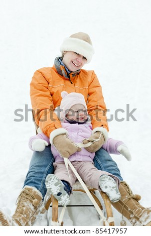 little girl sledding with mother
