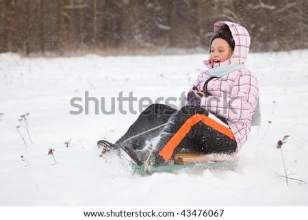 Little girl sledging down hill, bright winter scene
