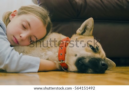 Little girl sleep embracing her dog on the parquet floor. Pet and child love.
