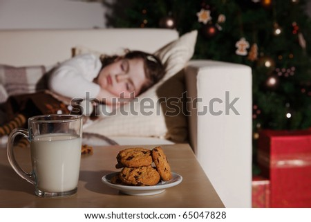 Little girl sleeping, and waiting for Santa Claus with a glass of milk and cookies