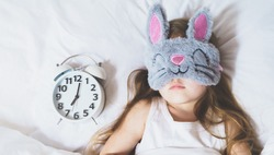 Little girl sleeping in bed under white blanket wearing grey bunny plush sleep mask with alarm clock on pillow. Early morning wake up. Putting kid to sleep.Mom's correct daily routine, rest for child.