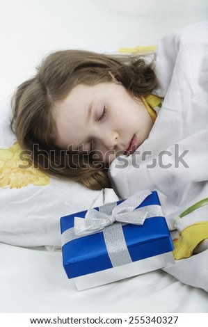 little girl sleeping in her bed with gift