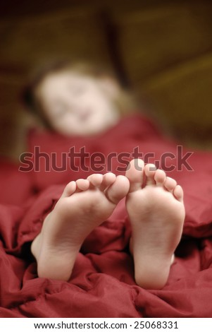 Little girl sleeping with feet poking out of blankets