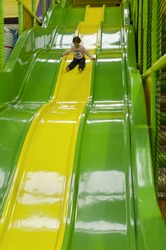 Little girl slid on a giant slid in indoor playground.