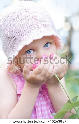 Little girl smelling a pink rose - stock photo