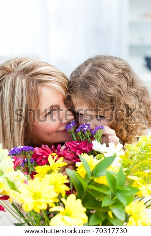 Little girl smelling flowers while her grandmother is smiling - stock photo
