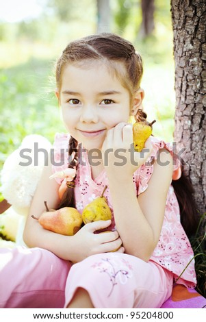 Little girl smiling and eating pears in the garden