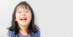 Little Girl Smiling and Laughing in the Camera on white background.Little asian girl smiling with perfect smile and white teeth.4 years old girl child showing front teeth with big smile.