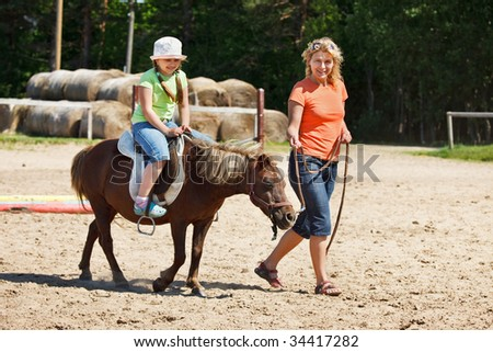 Little girl smiling and riding pony, woman leading pony by bridle