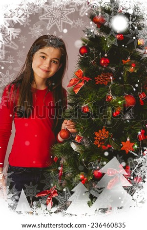 Little girl smiling at camera beside christmas tree against christmas theme frame in silver