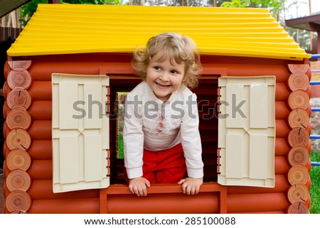 Little girl smiling in toy house window