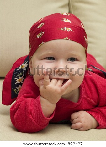little girl smiling with fingers in the mouth
