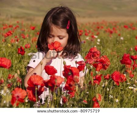 Little girl sniffing flowers in a poppy field