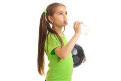 little girl soccer player drinks water from a bottle
