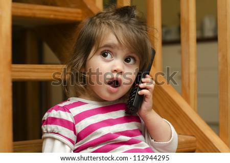 Little girl speak on the phone at home. Concept photo of long distance ,call ,communication, telephone, service, overseas, conversation, technology