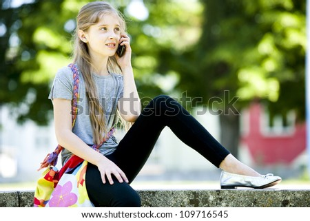 Little girl speaking on mobile phone outdoors