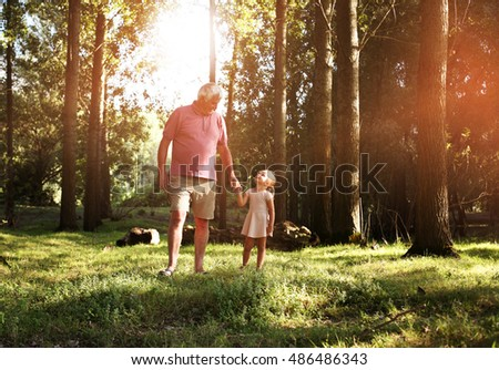 Little girl spending time with grandfather in the park.