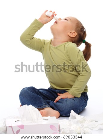 Little girl spraying her nose with nasal spray while sitting on floor, isolated over white