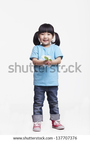 Little girl standing and holding a seedling, studio shot