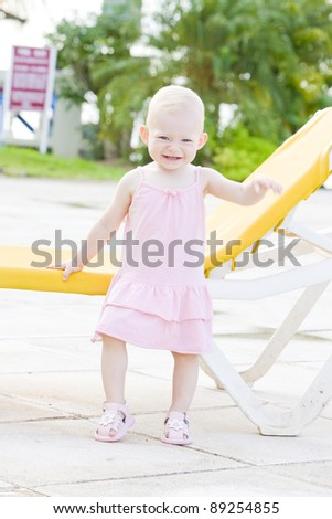 little girl standing at beach chair, Tobago - stock photo