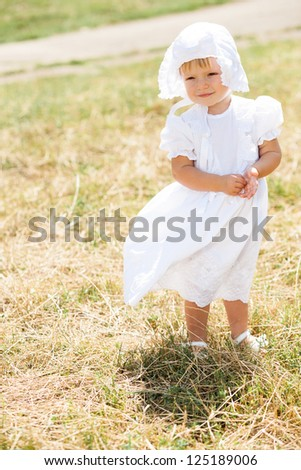 little girl standing in a field in white dress