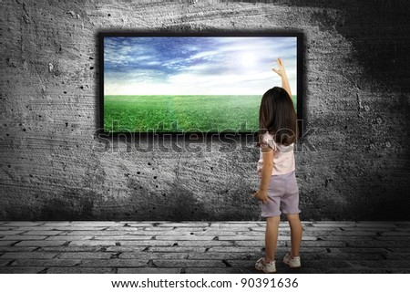 little girl standing in front of a large monitor on the background of gray walls