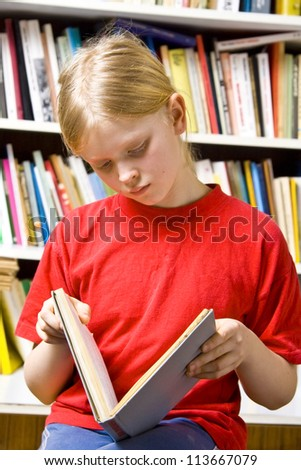 Little girl standing near the bookshelf